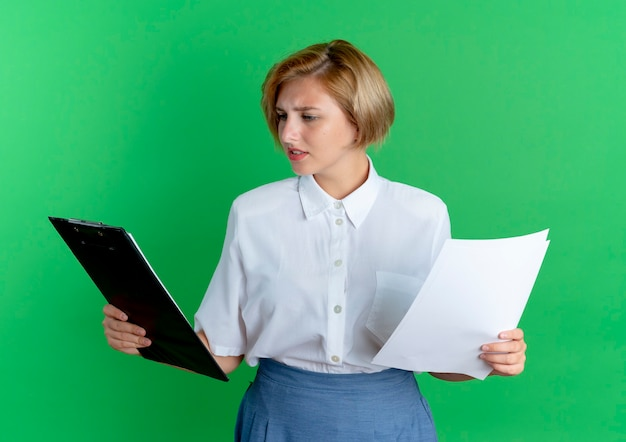 La giovane ragazza russa bionda confusa tiene i fogli di carta e guarda la lavagna per appunti isolata su fondo verde con lo spazio della copia
