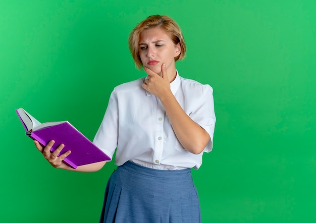 Молодая сбитая с толку русская блондинка кладет руку на подбородок, глядя на книгу, изолированную на зеленом фоне с копией пространства