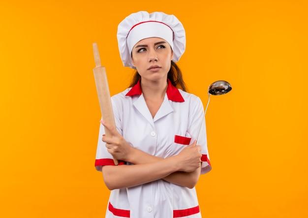 La giovane ragazza caucasica confusa del cuoco in uniforme del cuoco unico tiene il mattarello e il mestolo isolati sulla parete arancione con lo spazio della copia