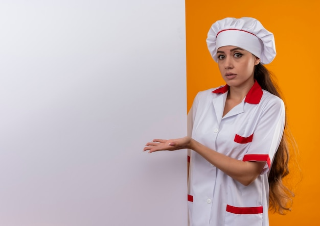 Young confused caucasian cook girl in chef uniform stands behind and points at white wall isolated on orange wall with copy space