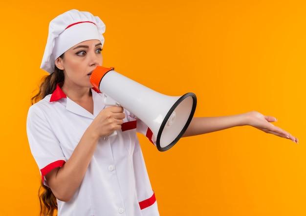 シェフの制服を着た若い混乱した白人料理人の女の子がスピーカーから話し、コピースペースのあるオレンジ色の壁に隔離された手を開いたままにします。