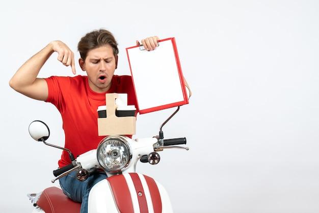 Uomo giovane corriere confuso in uniforme rossa che si siede sullo scooter che tiene ordini e documenti sulla parete gialla