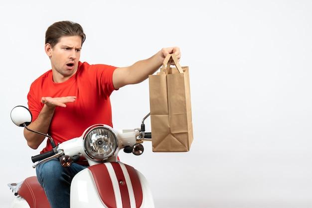Молодой смущенный эмоциональный курьер в красной форме сидит на скутере и держит бумажный пакет на белой стене