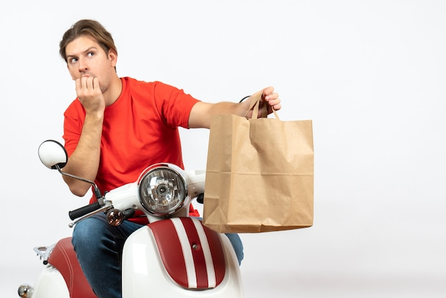 Young confused emotional courier guy in red uniform sitting on scooter giving paper bag on white wall