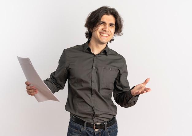 Il giovane uomo caucasico bello confuso tiene i fogli di carta bianca in bianco e guarda la macchina fotografica isolata su fondo bianco con lo spazio della copia