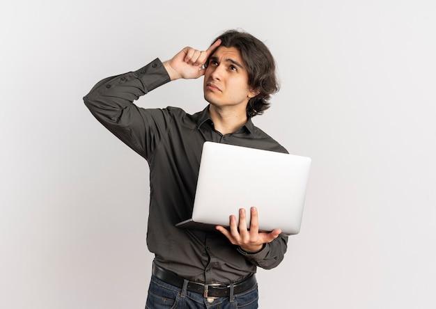 Молодой запутанный красивый кавказский мужчина кладет руку на голову и держит ноутбук на белом фоне с копией пространства