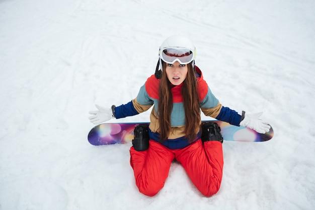 Молодой сбитый с толку сноубордист леди лежит на склонах морозным зимним днем