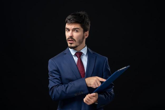 Giovane impiegato maschio confuso in vestito che tiene documenti sul muro scuro isolato