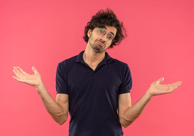 光学メガネと黒のシャツを着た若い混乱した男は手を上げてピンクの壁に孤立して見える