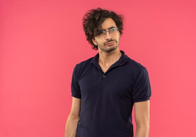 光学メガネと黒のシャツを着た若い混乱した男はピンクの壁に隔離された側を見て