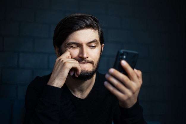 黒レンガの壁の背景にスマートフォンで探している若い混乱した男。