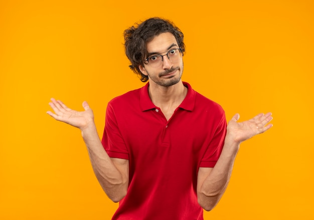 Young confused man in red shirt with optical glasses holds hands open isolated on orange wall