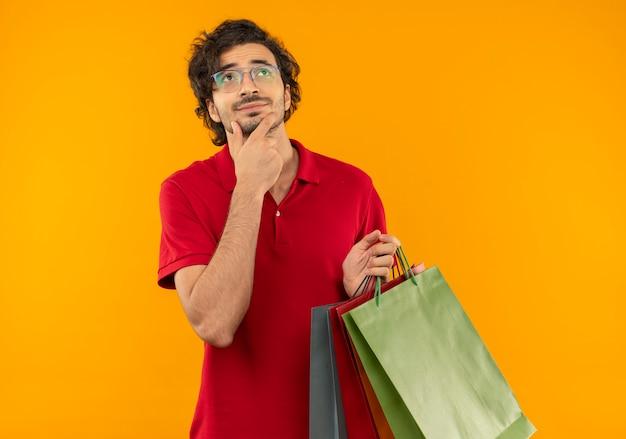 Giovane uomo confuso in camicia rossa con vetri ottici tiene sacchetti di carta multicolori e mette la mano sul mento isolato sulla parete arancione