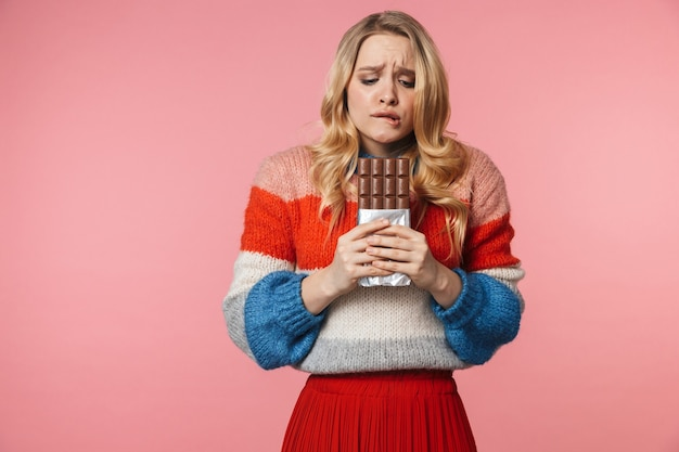 Young confused nervous pretty beautiful woman posing isolated over pink wall holding chocolate