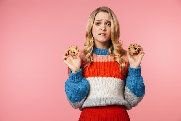 Young confused pretty beautiful woman posing isolated over pink wall holding sweet cookies
