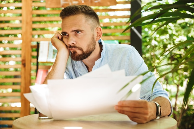 若い混乱した疲れた男が屋外で書類を持っています。