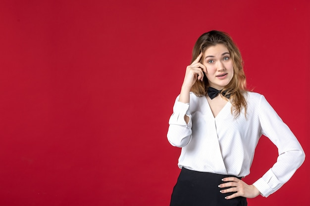 Young confused waitress woman butterfly on the neck on red background