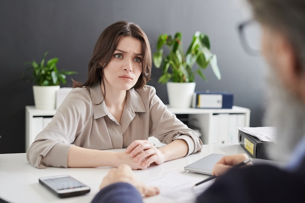 Young confused woman in formalwear looking at hr manager asking her personal question during discussion of resumer at interview