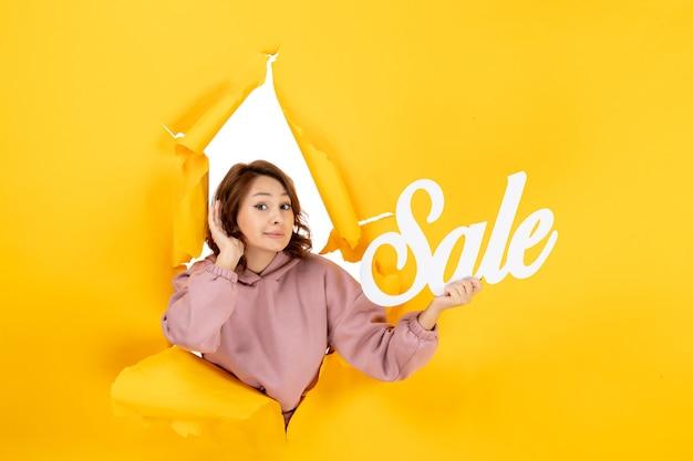 Молодая смущенная женщина слушает последние сплетни и держит знак продажи на желтом разорванном фоне
