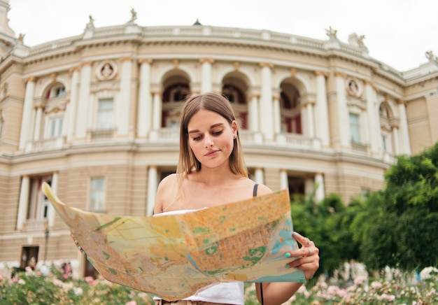 Young, confused woman tourist holds in her hands map of the city against the architecture of a tourist city.