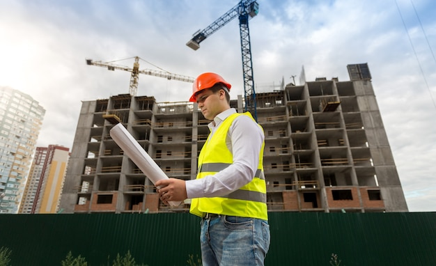 Young construction engineer in hardhat on building site with working cranes