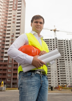 Young construction engineer in safety vest holding hardhat