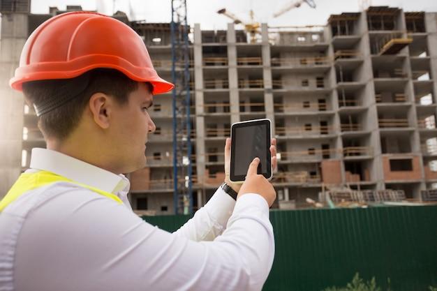建築現場でデジタルタブレットを使用する若い建設エンジニア