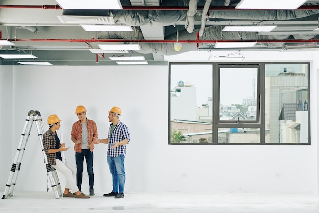 하드 모자와 평야 셔츠를 입은 젊은 건설 엔지니어가 직장에서 짧은 휴식 시간에 뉴스와 수군 거리를 논의합니다.