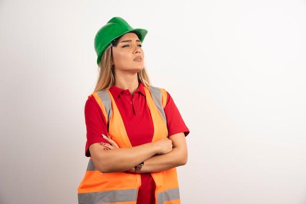 白い背景でポーズをとって緑のヘルメットの若い建設女性労働者。