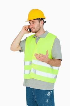 Молодой строитель обсуждает на мобильном телефоне