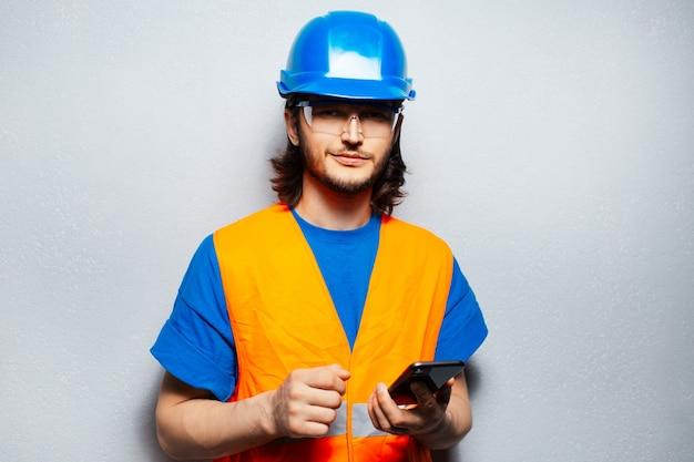 흰색 바탕에 전화를 들고 안전 장비를 착용하는 젊은 건설 노동자 엔지니어