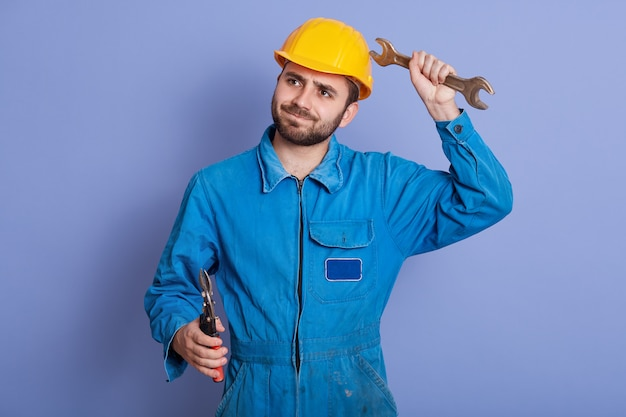 Young construction worker holding wrench tools in hands and looking aside with thoughtful facial expression