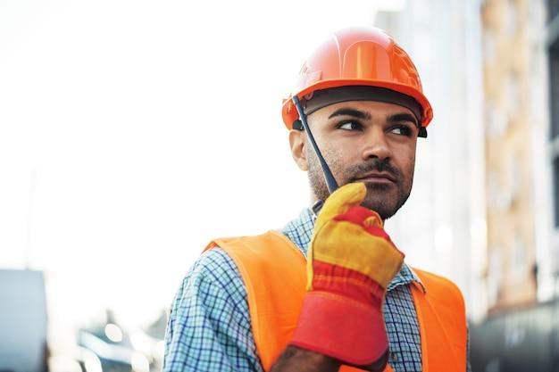 현장에서 무전기를 사용하여 제복을 입은 젊은 건설 노동자