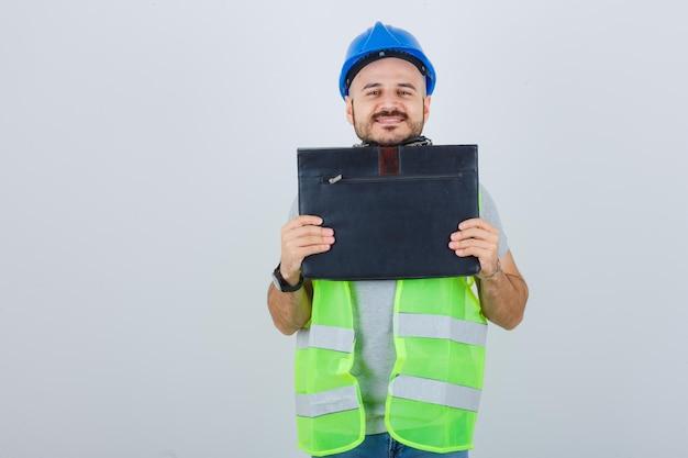 Giovane operaio edile che indossa un casco di sicurezza
