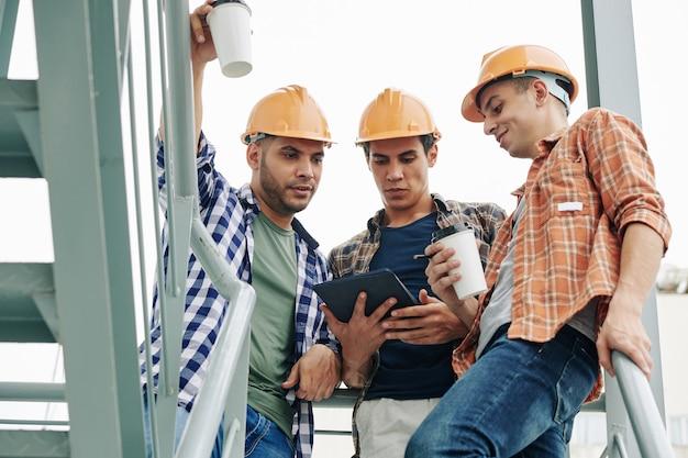 Молодые строители в касках пьют кофе на вынос и проверяют электронную почту подрядчика на планшетном компьютере