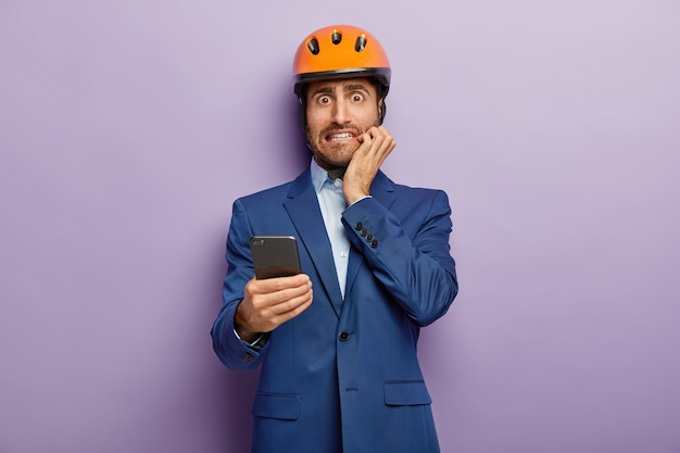Young constructor or architect wears safety helmet, uses cell phone and looks with embarrassement