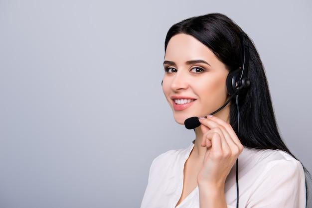 Молодой консультант в наушниках трогает микрофон и дает совет клиенту