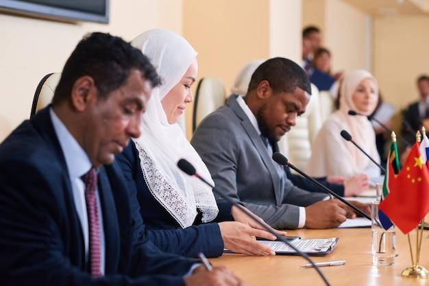 彼女の外国の同僚の間で文書を見てヒジャーブで若い現代のイスラム教徒の女性代表