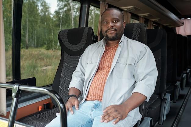 Молодой современный африканец, сидящий на переднем двойном сиденье