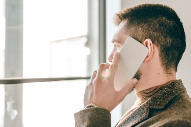 Young contemporary agent or broker in formalwear looking through window while consulting client on smartphone