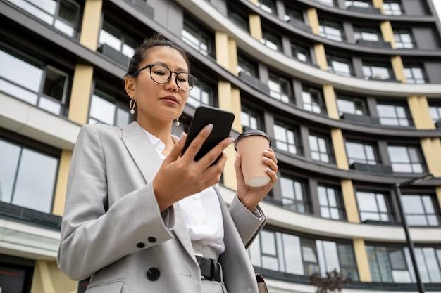 스마트폰 화면을 보고 있는 우아한 정장을 입은 젊은 현대 에이전트