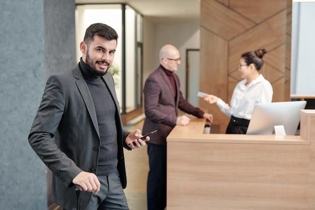 Молодой современный деловой путешественник с мобильным телефоном смотрит на вас во время вызова такси в лаундже отеля
