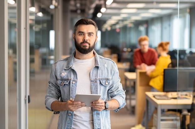 열린 공간 사무실 인테리어에 카메라 앞에 서있는 동안 디지털 태블릿을 사용하는 casualwear에서 젊은 현대 사업가