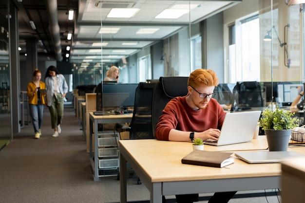 책상에 앉아 온라인 자료를 위해 인터넷에서 서핑하는 동안 노트북 디스플레이를보고 안경에 젊은 현대 사업가