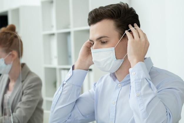 동료 옆에 앉아 있는 동안 사무실에서 안전하기 위해 보호 마스크를 얼굴에 씌우는 정장 차림의 젊은 현대 사업가