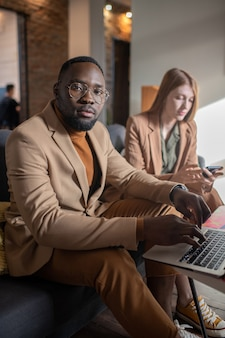 Young contemporary businessman looking at you while typing