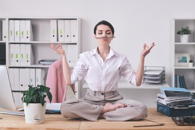 Молодая современная деловая женщина держит карандаш между носом и верхней губой, сидя в позе лотоса на столе и медитируя