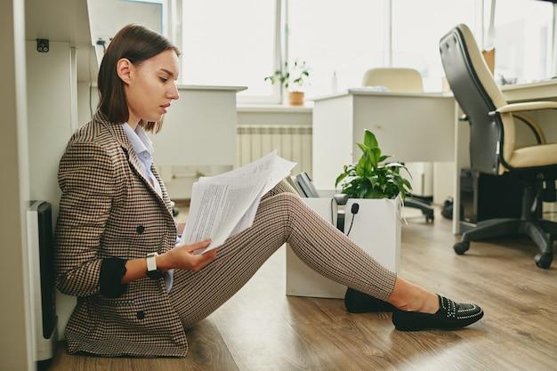 Молодая современная деловая женщина в элегантной повседневной одежде сидит на полу за столом и просматривает финансовые документы в офисе