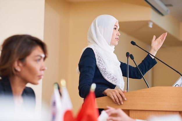 会議で外国のパートナーのためにトリビューンによってスピーチをするヒジャーブの若い現代の自信を持って女性政治家
