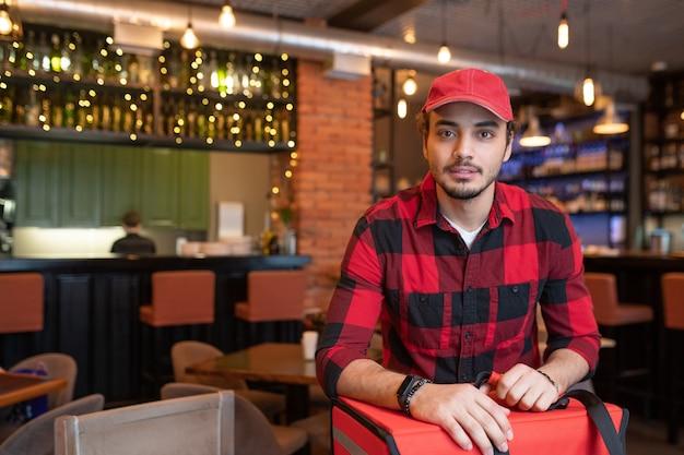 Молодой современный курьер в повседневной одежде, стоящий перед камерой в ресторане, собираясь доставлять заказы клиентам